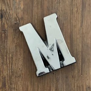 "5/$20 or FREE w/ purchase. Silver letter ""M"""